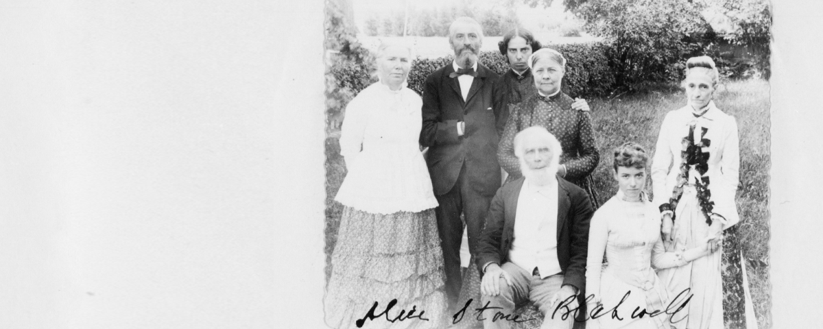 This black and white photograph probably shows (back row, left to right): Dr. Emily Blackwell, Mr. Ainsworth Spofford, Alice Stone Blackwell, and Lucy Stone; (front row, left to right): Henry Browne Blackwell, Florence Spofford and Mrs. Sarah (Partridge). Photo taken sometime between 1880-1893. The family are well dressed, but their clothing and hair are not overly ornate. Most of the women wear floral printed cottons and the men wear suits and ties typical of the period.