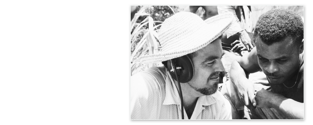 Photograph: Alan Lomax is on the left wearing headphones and a big straw hat. Ralph Hurtault sitting to the right of him is looking down and smiling. Both men are listening to audio playback. La Plane, Dominica. June, 1962