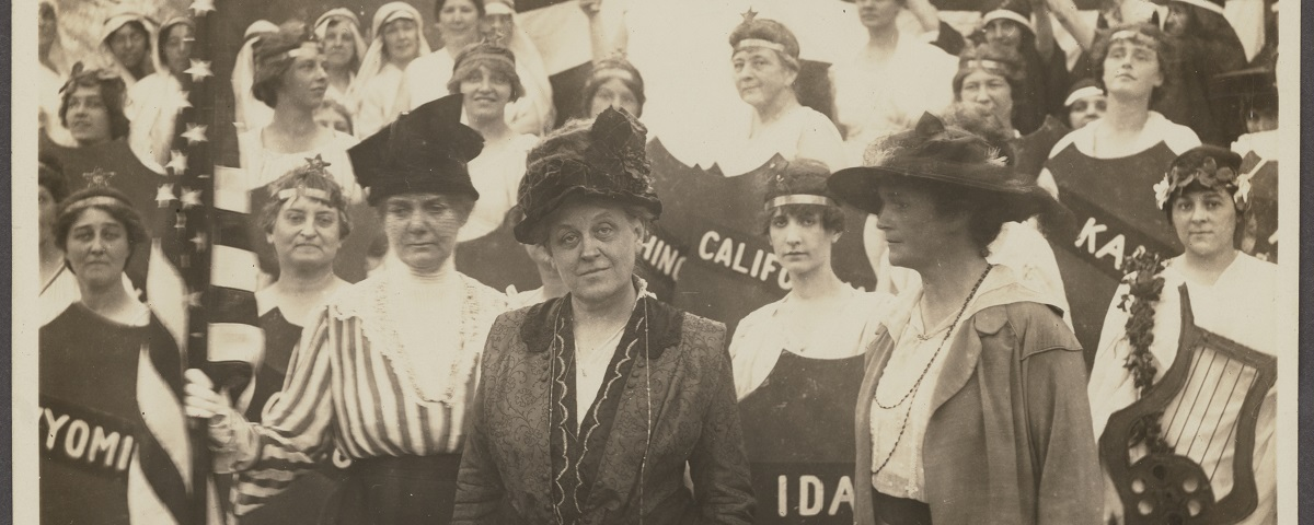 Carrie Chapman Catt stares defiantly at the camera. She is surrounded by women protesting for their right to vote. Some carry shields with state names on them, California, Wyoming, Kansas. Others carry American flags.